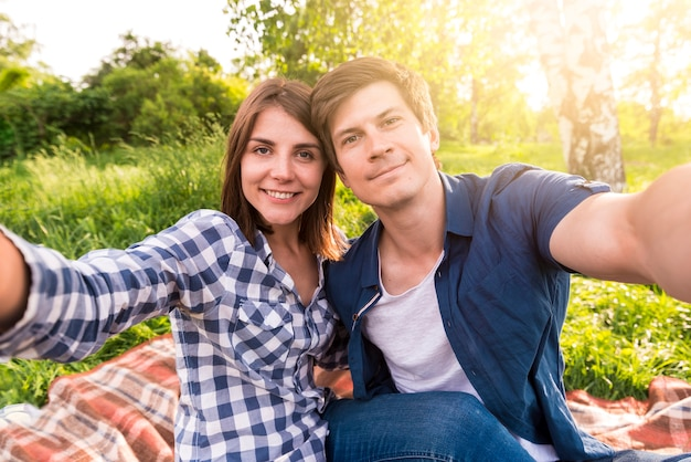 Young lovers sitting on plaid in forest and taking selfie Free Photo
