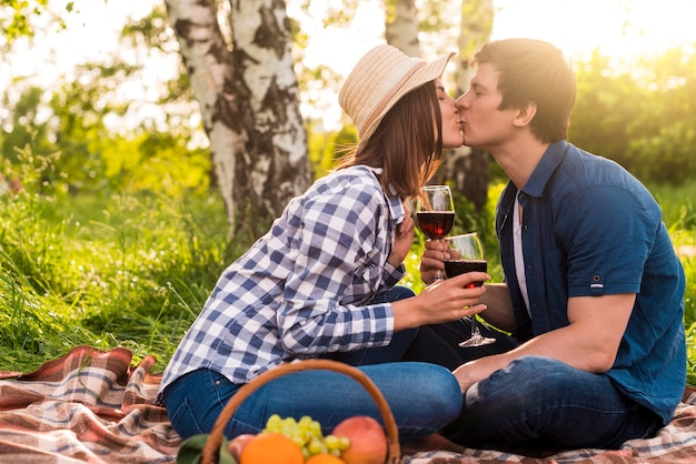 Young lovers sitting on plaid and kissing Free Photo
