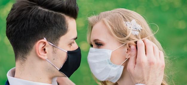 結婚式の日の検疫中に公園で医療マスクで歩く若い夫婦。コロナウイルス、病気、保護、病気、病気のインフルエンザのヨーロッパのお祝いはキャンセルされました。 Premium写真