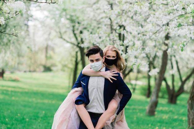 結婚式の日の検疫中に公園で医療マスクで歩く若い夫婦。 Premium写真