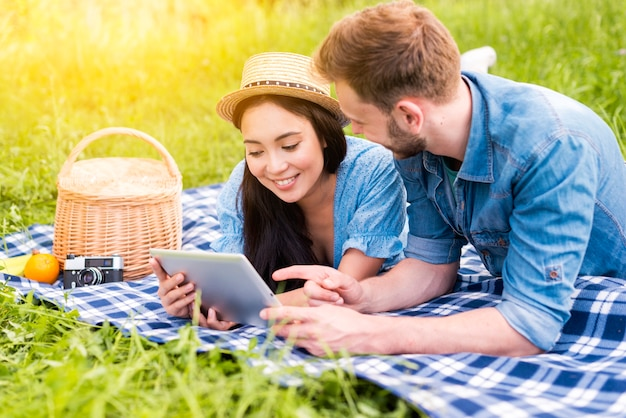 Young loving couple web surfing using tablet in countryside Free Photo