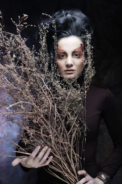 乾燥したツイの束を保持している明るい化粧の若い高級女性 Premium写真