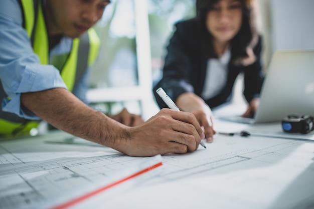 젊은 남성과 여성 건축가 동료가 교육 수업 중 조언을 제공하고 실수를 수정하는 재능있는 교사와 협력하여 인테리어 제작 프로젝트의 그래픽 계획을 그리기 프리미엄 사진