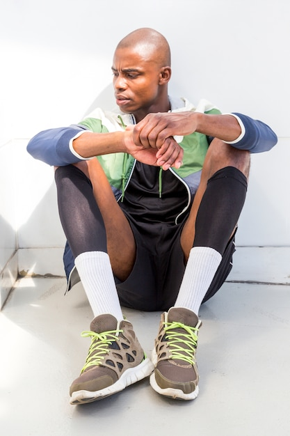A young male athlete sitting on ground looking away Free Photo