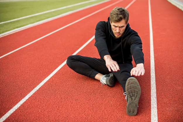 Young male athlete sitting on race track stretching his hand and legs Free Photo