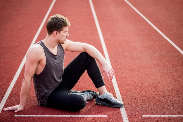 Young male athlete sitting on the racetrack start line Free Photo