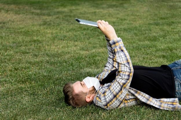 Молодой мужчина просматривает планшет на открытом воздухе Бесплатные Фотографии
