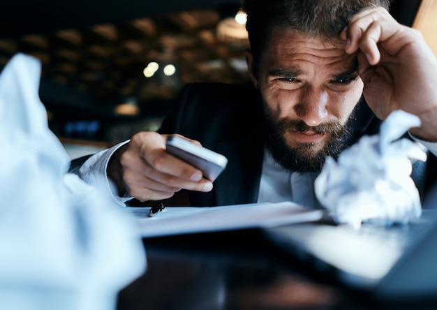 Молодой бизнесмен-мужчина сидит за столом с бумагами и с нетерпением ждет Premium Фотографии