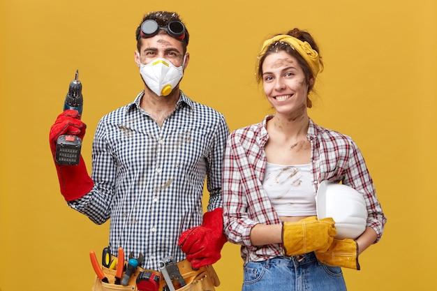 Молодой плотник в защитных очках и маске, держащий буровой станок, оснащенный различными инструментами для строительства, стоит рядом с женой с довольным выражением лица во время работы Бесплатные Фотографии