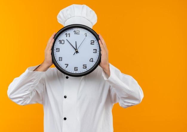 Giovane cuoco maschio in uniforme del cuoco unico che tiene e che si nasconde dietro l'orologio isolato sullo spazio arancione Foto Gratuite