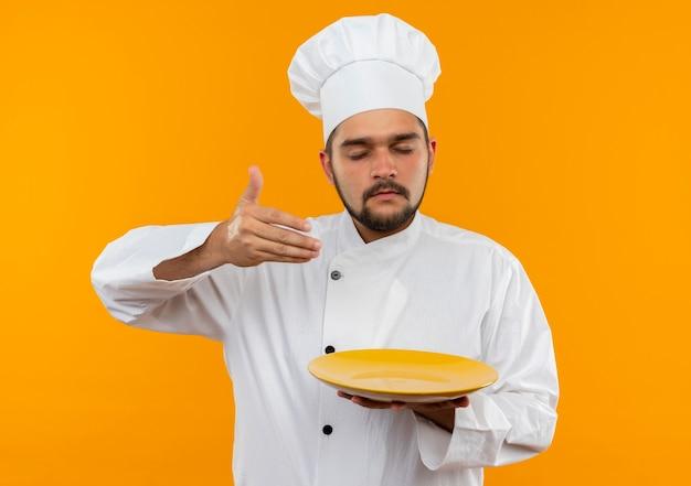 Giovane cuoco maschio nel piatto della tenuta dell'uniforme del cuoco unico e annusando con la mano sull'aria e gli occhi chiusi isolati sullo spazio arancione Foto Gratuite