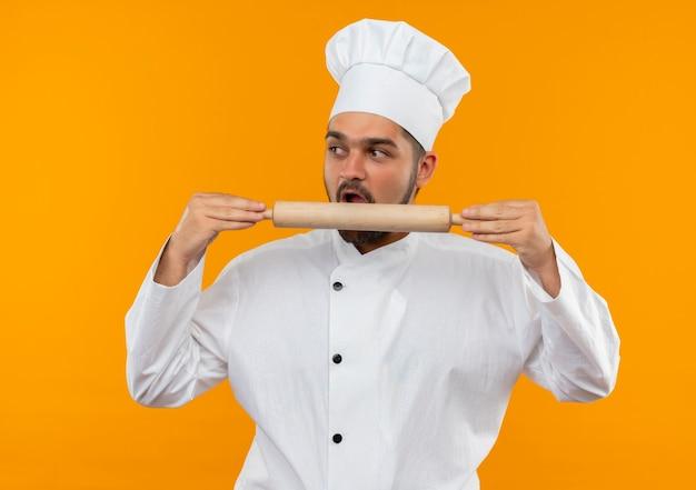 Молодой мужчина-повар в униформе шеф-повара держит и пытается укусить скалку и смотрит в сторону, изолированную на оранжевом пространстве Бесплатные Фотографии