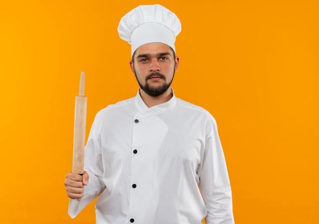Молодой мужчина-повар в униформе шеф-повара держит скалку на оранжевом пространстве Бесплатные Фотографии