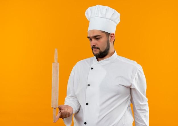 Молодой мужчина-повар в униформе шеф-повара держит скалку на пальце и смотрит на нее, изолированной на оранжевом пространстве Бесплатные Фотографии