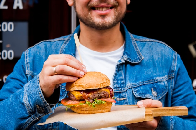A young male cook is holding a handmade hamburger with meat and vegetables. Premium Photo