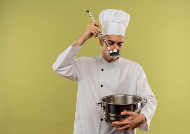 コピースペースでスープを試して鍋を保持しているシェフの制服を着た若い男性料理人 無料写真