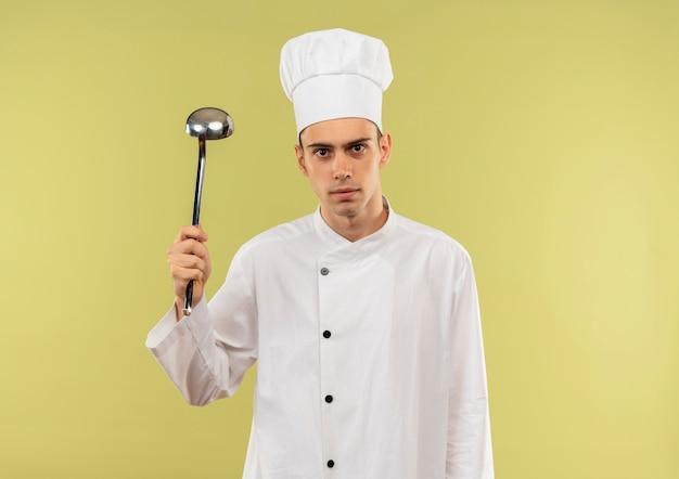 コピースペースのある孤立した緑の壁に手に鍋を上げるシェフの制服を着た若い男性料理人 無料写真