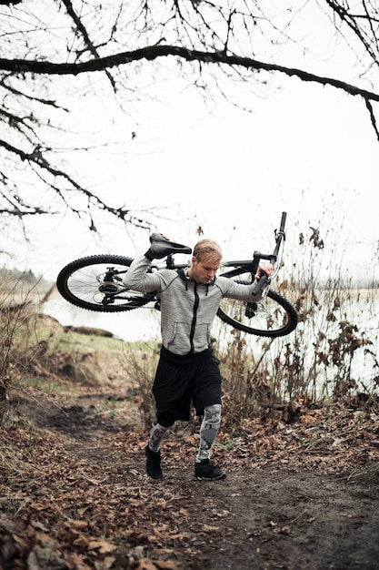 Young male cyclist carrying his mountain bike Free Photo