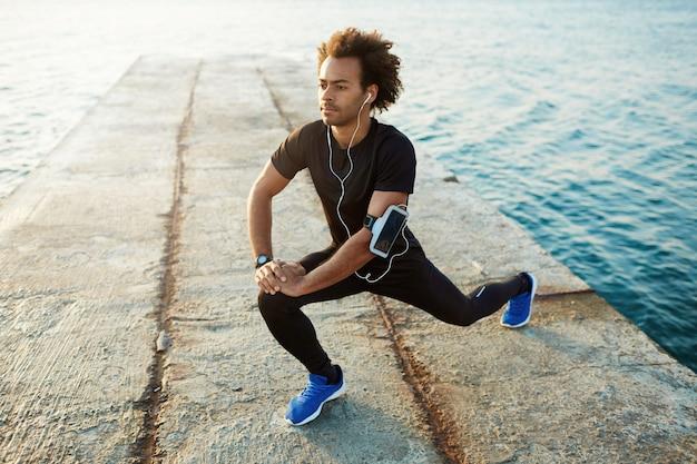 若い男性の浅黒い肌のランナーで、フィットボディが美しく、筋力トレーニングの前に筋肉をウォーミングアップします。 無料写真