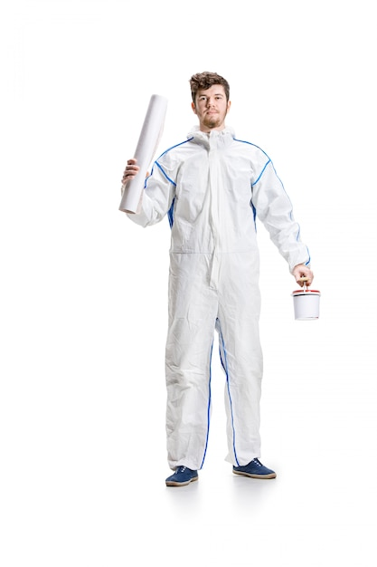 Young male decorator painting with a paint roller on white wall. Free Photo