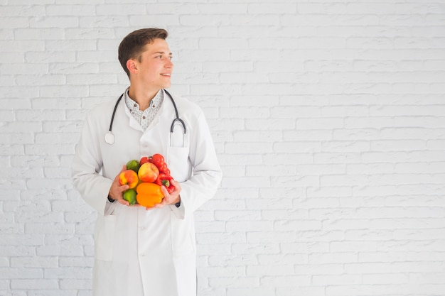 Young male doctor standing against the wall holding healthy food looking away Free Photo