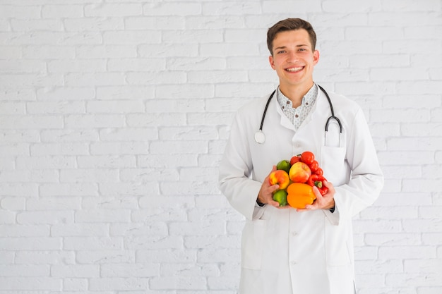 Young male doctor standing against the wall holding healthy food Free Photo