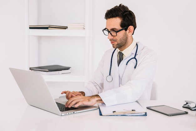 Young male doctor wearing eyeglasses using laptop in clinic Free Photo