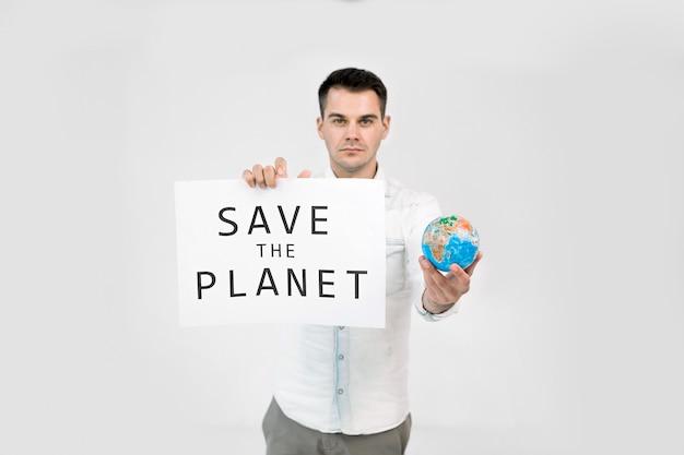 Молодой мужчина-эколог держит бумажный плакат с текстом «спасите землю» Premium Фотографии