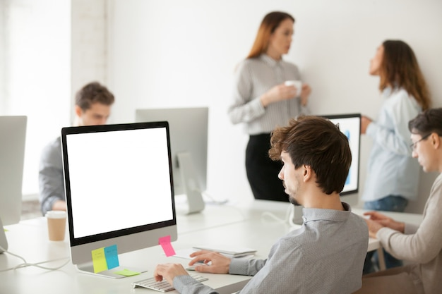 Young male employee working on computer writing email in office Free Photo
