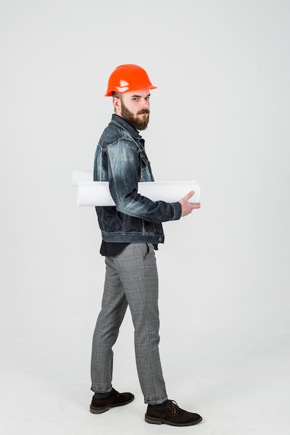 A young male engineer holding blueprints in his hand Free Photo
