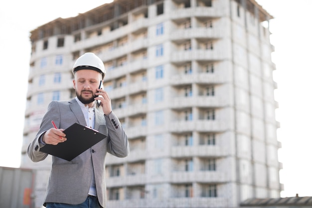 Young male engineer talking on cellphone while holding clipboard at construction site Free Photo
