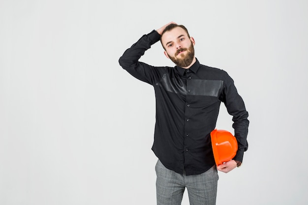 Young male engineer with hand on his head holding hardhat Free Photo