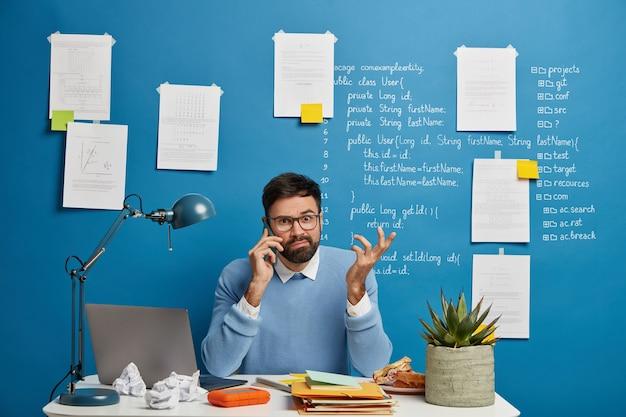 Молодой предприниматель-мужчина обдумывает бизнес-решение во время телефонного разговора, смущенно поднимает руку, сидит за белым столом с блокнотами, мятой бумагой и портативным компьютером Бесплатные Фотографии