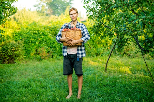 Young male farmer holding a basket with collected harvest fruits and vegetables in a garden farm Premium Photo