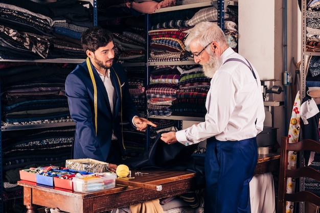 Young male fashion designer showing blue fabric to his customer in the shop Free Photo