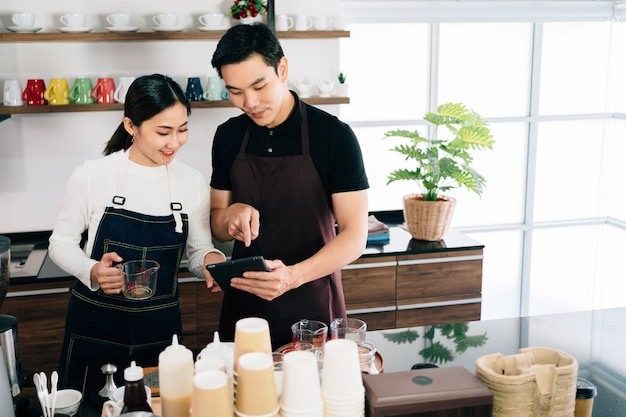 Young male and female barista cafe owner standing inside the coffee counter and talking about customer order from a tablet with smiles. Premium Photo