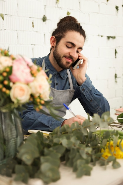 Young male florist noting client order during mobile phone conversation in flower shop Free Photo