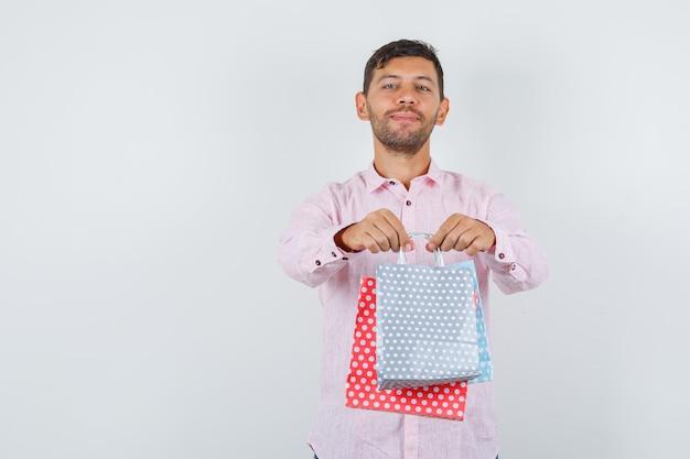 젊은 남성 셔츠에 종이 가방을주고 쾌활한, 전면보기를 찾고 있습니다. 무료 사진