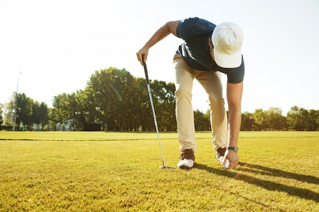 Young male golfer placing golf ball on a tee Free Photo