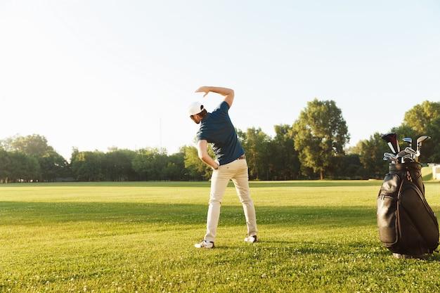 Молодой гольфист мужского пола растягивает мышцы перед началом игры Бесплатные Фотографии