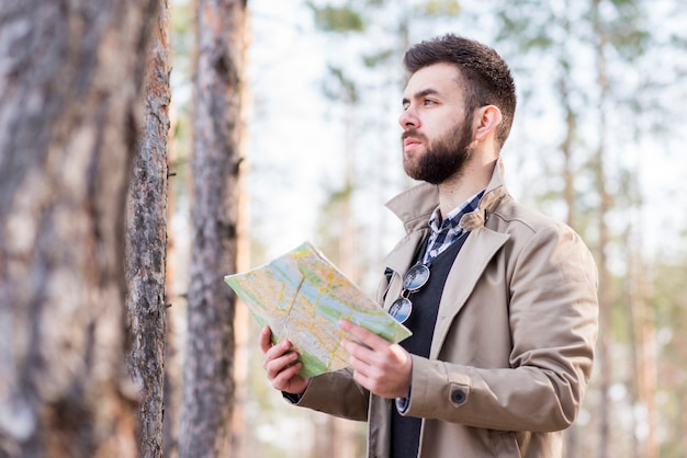 Young male hiker standing in the forest holding map in hand Free Photo