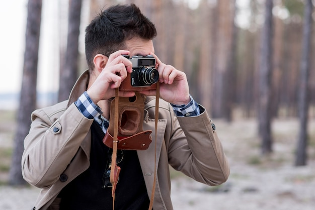 Young male hiker taking photos with camera Free Photo