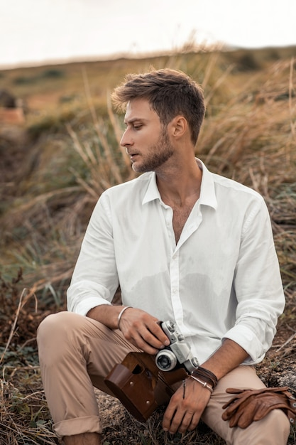 Young male hipster in a white shirt with old camera in his hands posing in the nature. explore unknown and look cool in strange scenery. Premium Photo