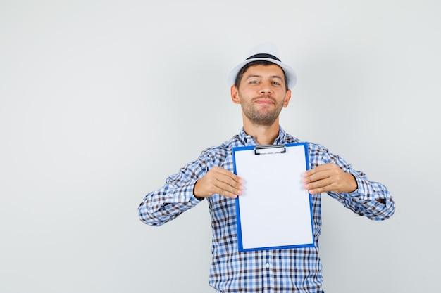 クリップボードを保持し、チェックシャツで笑っている若い男性 無料写真