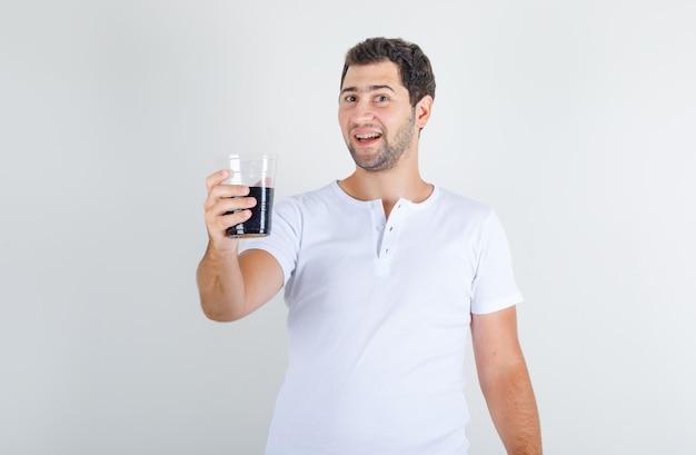 Молодой мужчина держит напиток колы в белой футболке и выглядит счастливым Бесплатные Фотографии