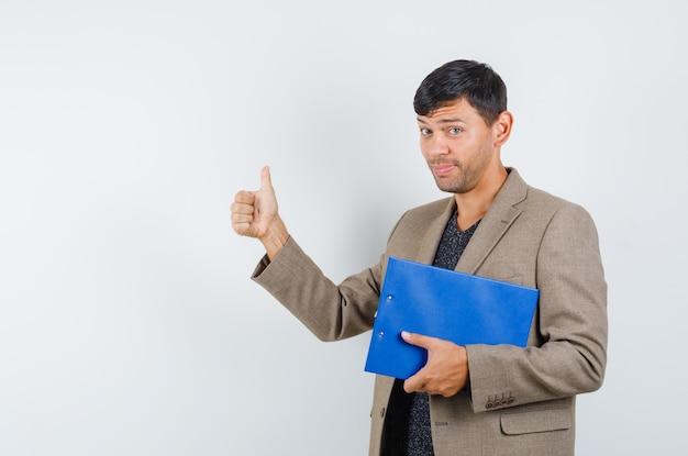 灰色がかった茶色のジャケット、黒のシャツで親指を表示し、感謝している、正面図を表示しながらノートを保持している若い男性。 無料写真