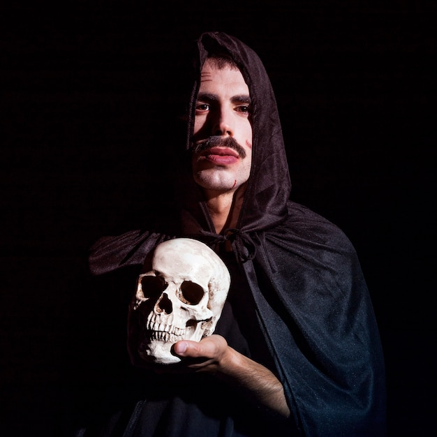 Young male in hooded cape holding skull Free Photo