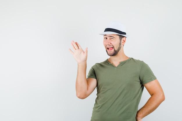 緑のtシャツと帽子をかぶった若い男性が手を振って、目をまばたき、舌を突き出して、面白そうに見える 無料写真