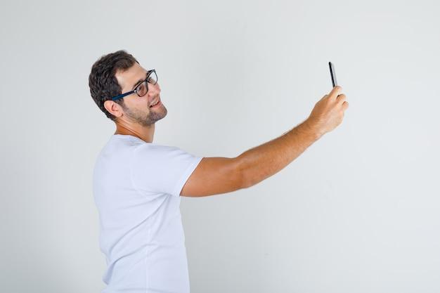 白いtシャツ、スマートフォンでselfieを取ってうれしそうなメガネの若い男性 無料写真