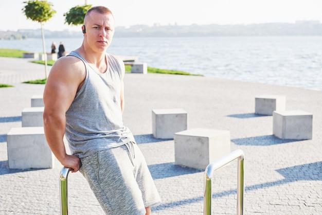 Giovane atleta maschio pareggiatore formazione e facendo allenamento all'aperto in città. Foto Gratuite